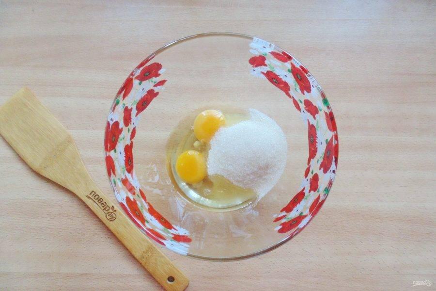 В миску выложите яйца и сахар.