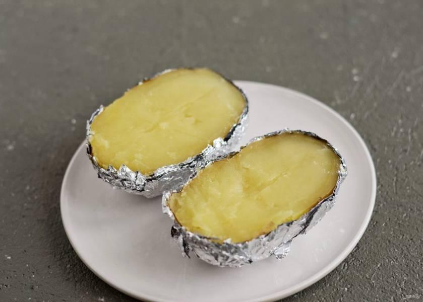 Разрежьте картофель прямо в фольге пополам.