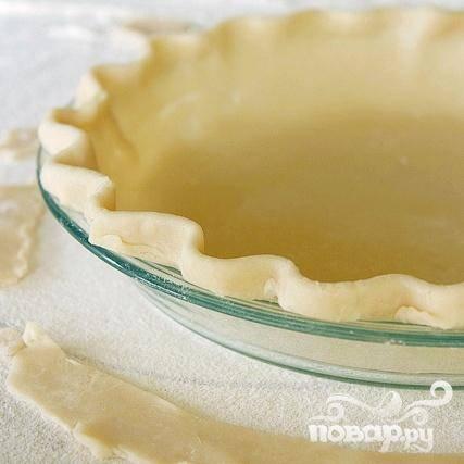 2. Раскатать корочку для пирога, следуя инструкциям на упаковке, и выложить  форму диаметром около 23 см. Обрезать лишнее и декоративно оформить края.