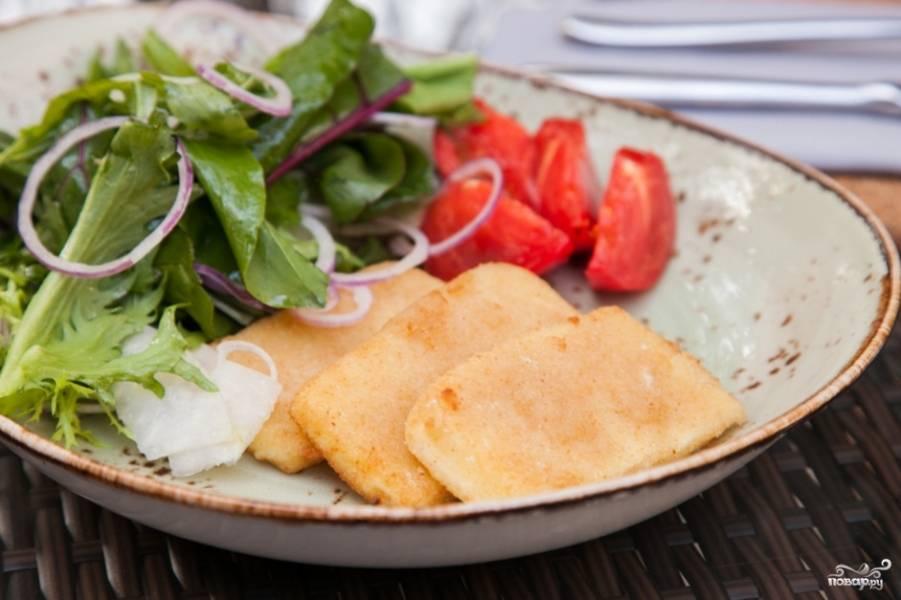 Готовые ломтики обжаренного в панировке сыра сулугуни выложите на блюдо с салатом. Сразу же подавайте к столу, пока сыр горячий. Если он остынет, то перестанет быть жидким, а корочка не будет хрустеть, так как она быстро отсыревает.