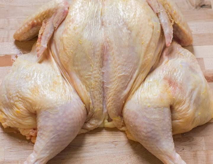 Надавите ладонью на то место, откуда удалили хребет, чтобы курица раскрылась как книжка и стала плоской как на фото.
