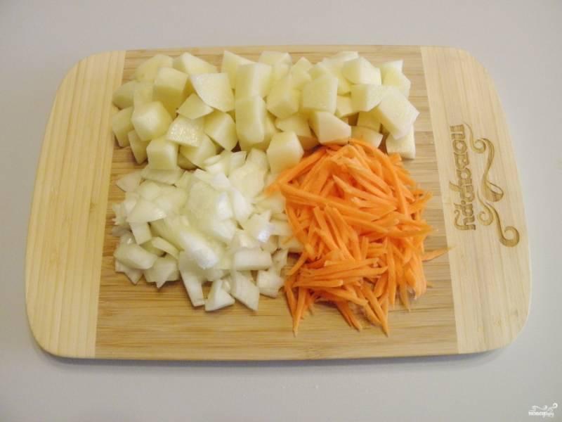 Когда бульон будет готов, вымойте и очистите все овощи: лук и картофель порежьте кубиками, морковь  натрите на крупной терке.