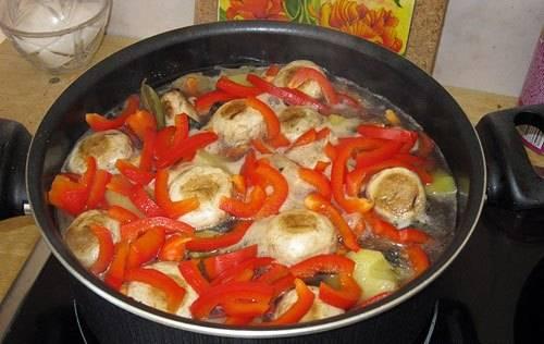 4. Когда все ингредиенты потушатся вместе, доливаем бульон или воду, чтобы покрыла баклажаны. Добавим теперь грибы целиком и порезанный перец. Томим до готовности перца.