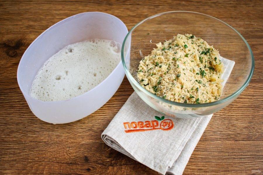 В одной миске смешайте панировочное сухари, тертый сыр, сушенную петрушку, чеснок, соль, перец. В другой миске взбейте белки с помощью вилки или венчика.