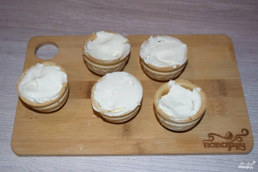 Наполните тарталетки крем-сыром. При отсуствии крем-сыра можно взять сметану, предварительно выложив ее на марлю. Сметана спустит сыворотку и станет близкой к крем-сыру. Крем-сыр можно приготовить и самостоятельно.