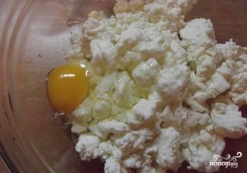 В миске смешайте творог с яйцом и сахаром.