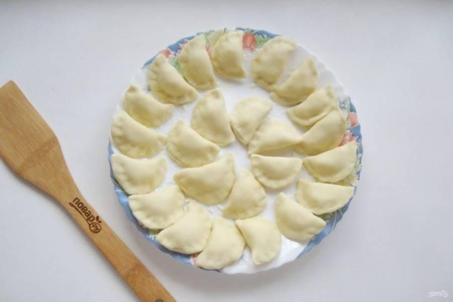 Слепите вареники и выложите на тарелку, присыпанную мукой.