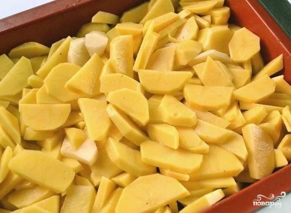 Теперь смазываем формы для запекания сливочным маслом и выкладываем на нее кусочки картофеля.