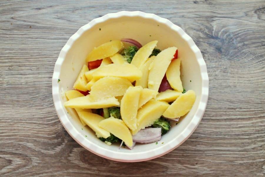 Добавьте в миску с овощами отварной картофель. Влейте растительное масло и аккуратно перемешайте.