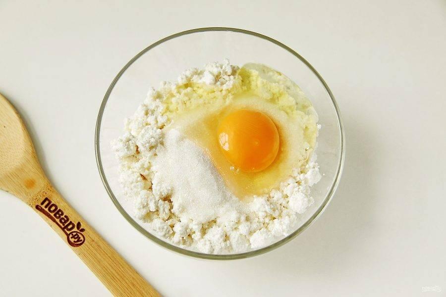 Добавьте к творогу яйцо и сахар.