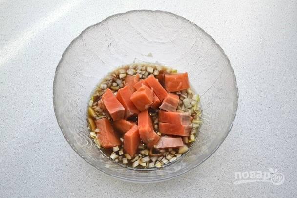 Красную рыбку промойте, обсушите и нарежьте филе небольшими кусочками. Выложите их в маринад, аккуратно перемешайте и оставьте на 30 минут.