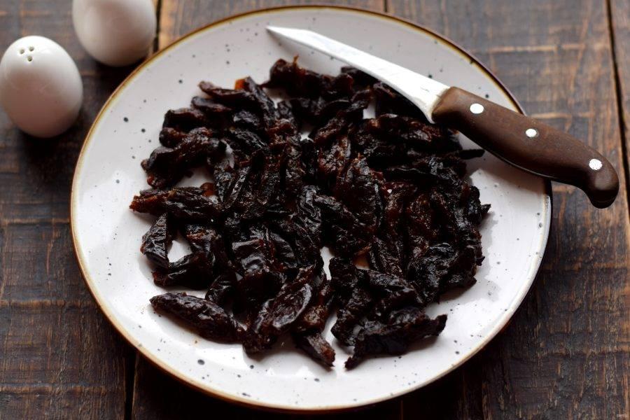 Мягкий чернослив нарежьте одинаковыми полосками. Очень твердый чернослив необходимо заранее распарить в кипятке до мягкости, затем просушить и нарезать.