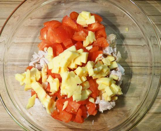 Теперь приступаем к помидорам, их также нужно вымыть и нарезать на кусочки, сильно мельчить не старайтесь, поскольку лишняя вода нам в салате не нужна и вместе с курицей их уже можно поместить в салатницу.