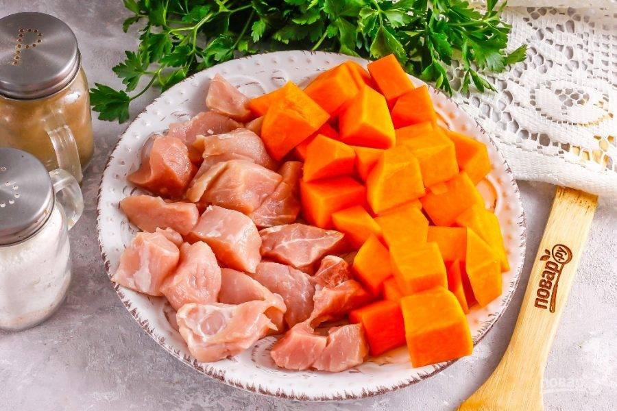 Промойте мясо в воде, срежьте жилы и пленки. Тыкву очистите от кожуры, промойте в воде. Нарежьте мясо и тыкву средними кубиками.
