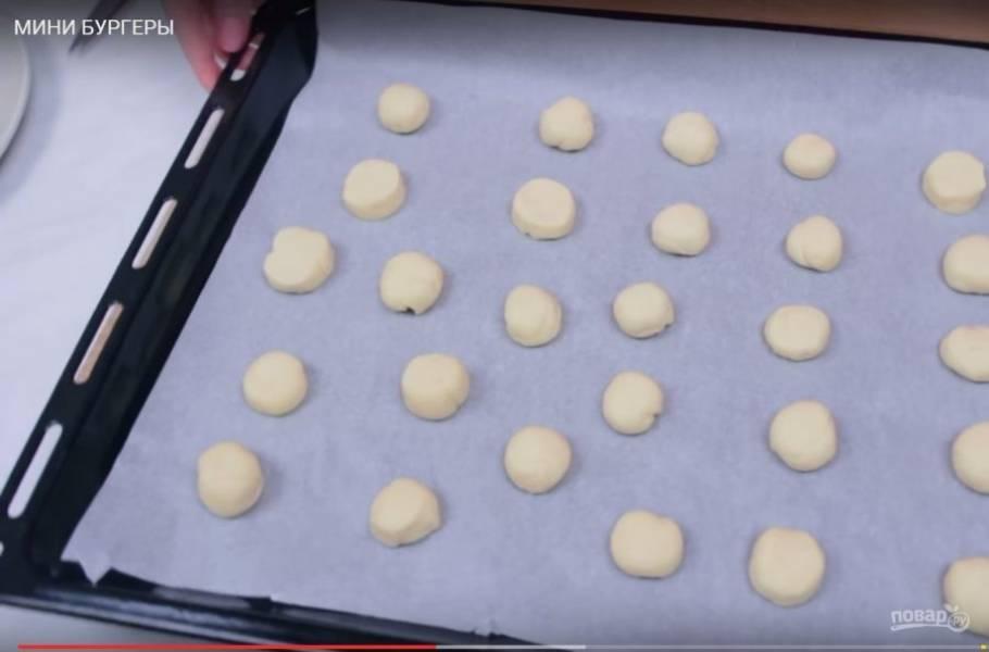 3. Затем сформируйте из теста небольшие кружочки и выложите их на застеленный пергаментной бумагой противень. Накройте их полотенцем и оставьте еще на полчаса. Посыпьте булочки кунжутом и выпекайте в разогретой до 180 градусов духовке 12-15 минут.