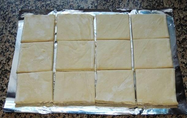 Размораживаем готовое слоеное тесто и разрезаем каждую пластину (всего их 2) на 6 квадратиков.