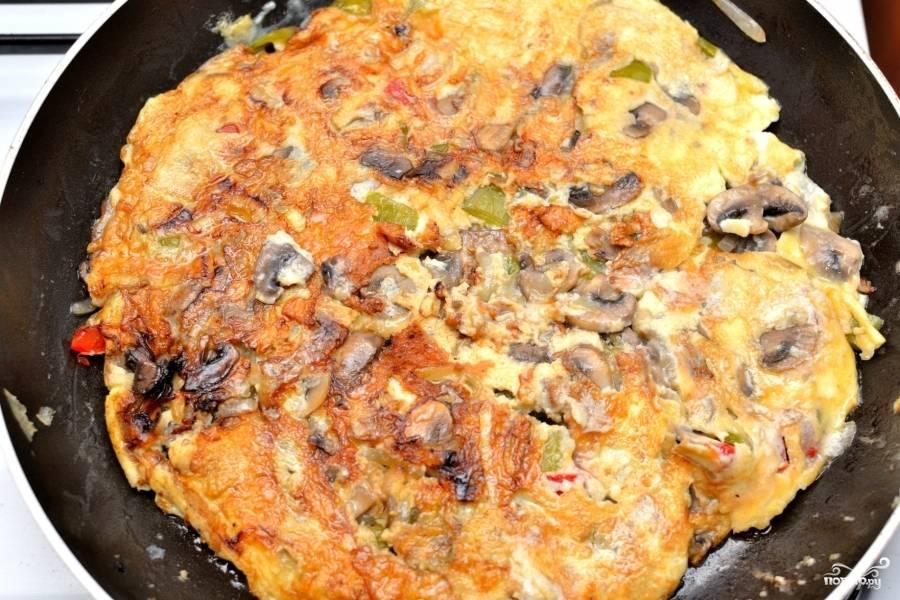 Переворачивайте аккуратно, чтобы овощи и грибы не вывалились, а омлет не разорвался.