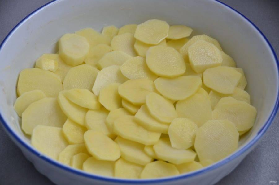 Ломтиками нарежьте картофель и выложите его в форму для запекания.