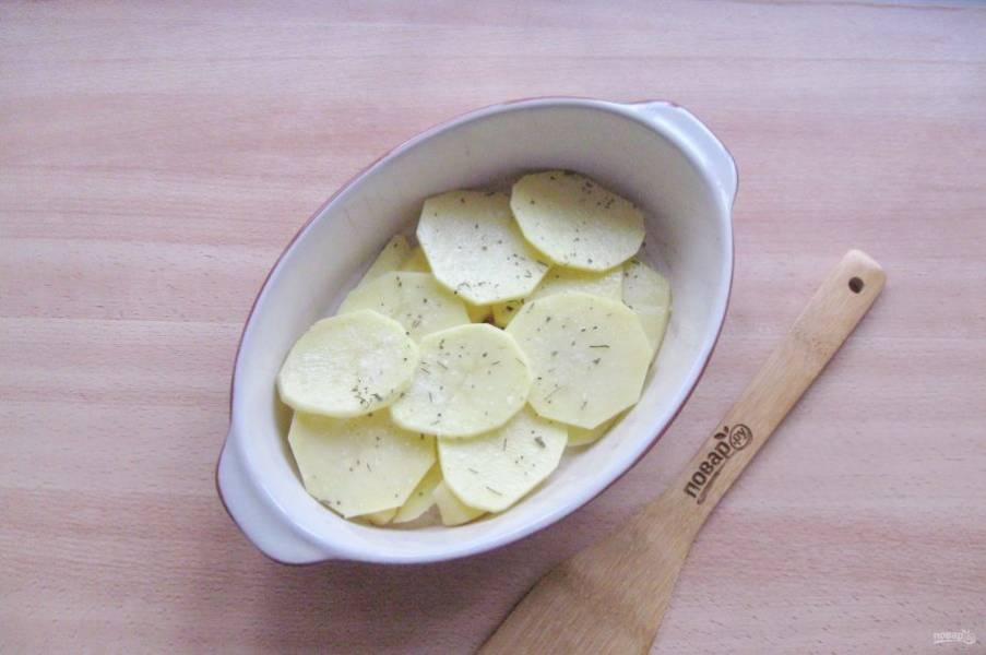 Картофель очистите, помойте и нарежьте пластинками. Половину картофеля выложите в форму для запекания. Посолите и поперчите по вкусу.