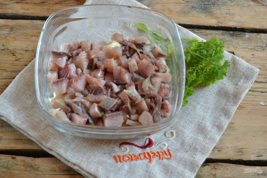 Селедку порежьте мелкими кубиками и выложите сверху на картофель. Сверху смажьте толстым слоем майонеза.