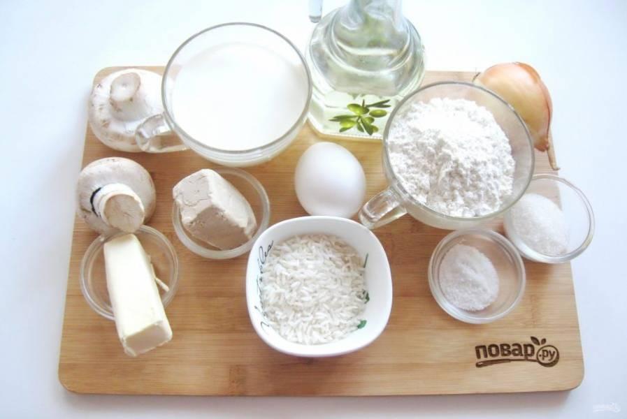 Для приготовления таких пирожков возьмите следующие продукты: яйца, молоко, дрожжи, сахар, соль, масло сливочное и подсолнечное, муку, рис, шампиньоны, лук репчатый.