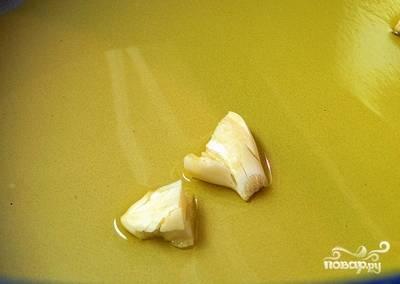 В разогретое на сковороде масло бросить чеснок и жарить 2 минуты для аромата..