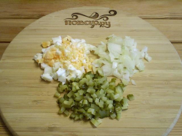 Отварите яйцо, очистите от скорлупы. Порежьте мелко лук кубиками, яйцо и огурцы.