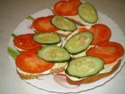Уложите на хлеб ломтик помидора и огурца.