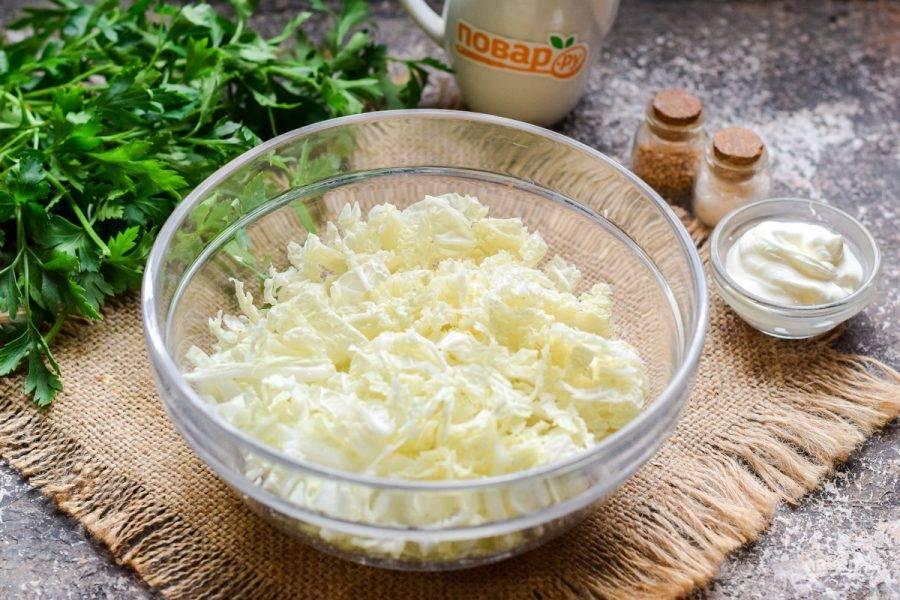Пекинскую капусту нарежьте тонкими полосками. Подготовьте глубокую миску для салата, переложите капусту в емкость.