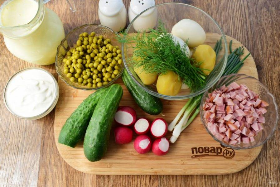 Картофель отварите в течение 30 минут, остудите немного, очистите. Яйца отварите в течение 5 минут, остудите в холодной воде, очистите. Слейте маринад с консервированного зеленого горошка. Зелень, огурцы и редис вымойте. Ветчину нарежьте мелкими кубиками.