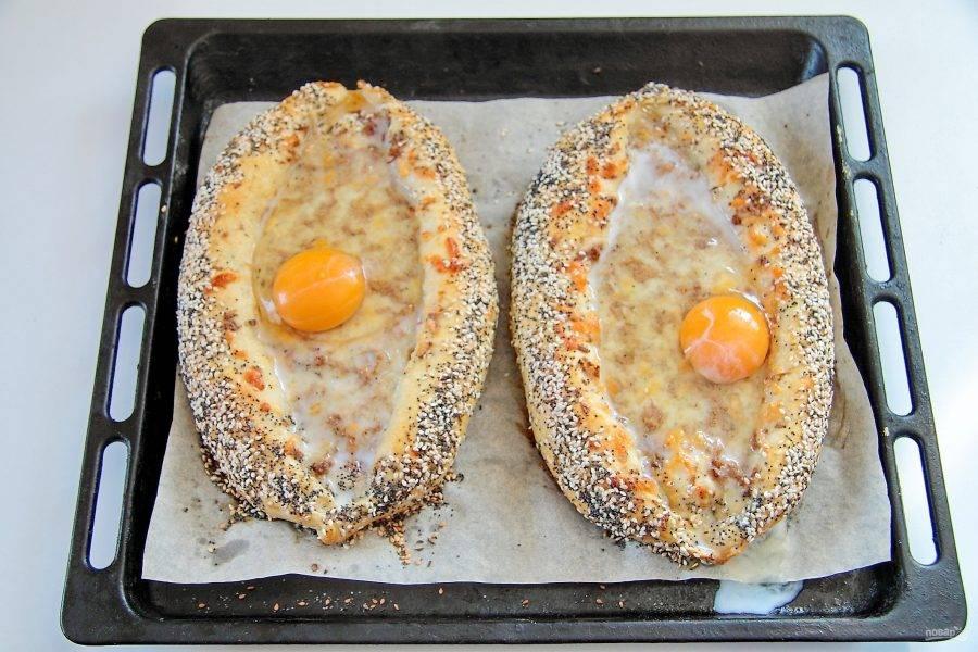 Выпекайте при 180 градусах до золотистого цвета. Затем хачапури необходимо достать и в каждую лодочку разбить по яйцу.