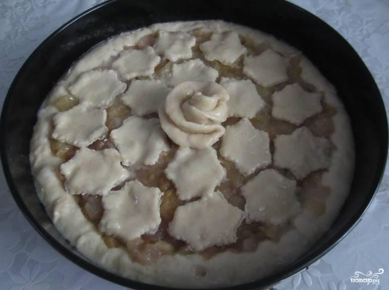 Из оставшегося теста сформируйте фигурные украшения. Оставьте будущий пирог в теплом месте на 30 минут. Смажьте верхушку яйцом. Теперь можно отправлять пирог в духовку на 45 минут, температура — 180 градусов.