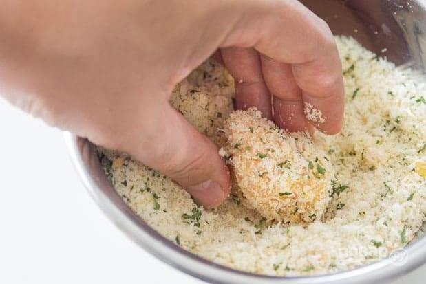 6.В третью миску добавьте тертый пармезан, измельченную петрушку и панировочные сухари, после яйца отправьте кусочек в эту смесь.
