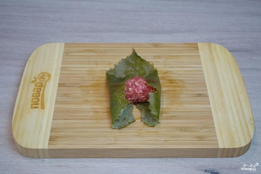Приподнимите края листика и сформируйте долминку, обкрутив лист вокруг начинки.