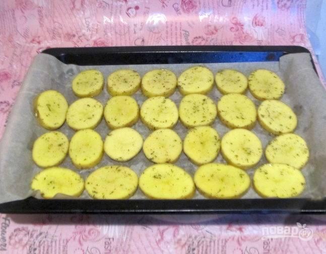 В емкости перемешайте картофель с маслом, луком, посыпьте тимяном и солью. Разложите картофель на противень одним слоем вплотную друг к другу.