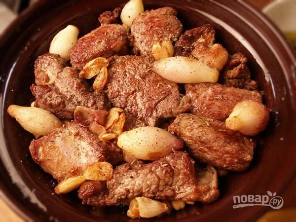 Поверх нута выложите обжаренное мясо с луком и чесноком. Полейте сверху образовавшимся при жарке соком. Посыпьте приправами, специями и солью.
