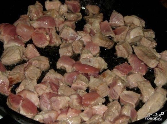 На горячей сковороде разогрейте четверть стакана растительного масла и выложите порезанное мясо.