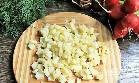 Промытый картофель отварите до готовности в подсоленной воде. Затем остудите его, почистите и мелко нарежьте.