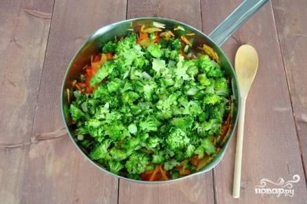 Брокколи нарежем на маленькие кусочки, добавим к овощам и обжарим минуты 1.5.