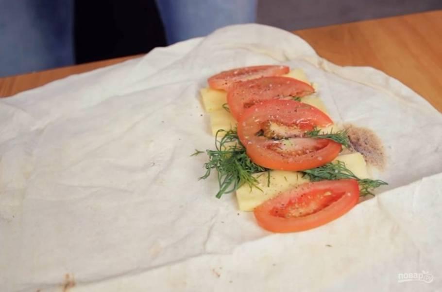 2. Далее разделите лаваш на две части. Сбоку посередине выложите нарезанный сыр, помидоры и зелень, посолите и поперчите по вкусу.