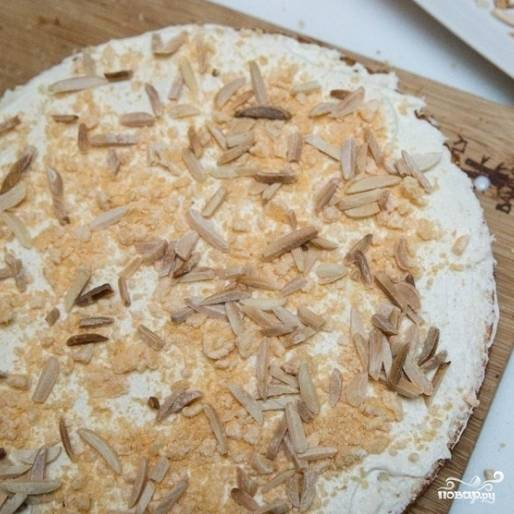 9. Нижний слой бисквита выложите на блюдо, смажьте его четвертой частью крема, выложите измельченный миндаль и измельченные вафли.