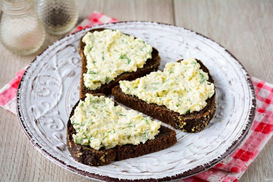 Хорошо смажьте хлеб сырной пастой.