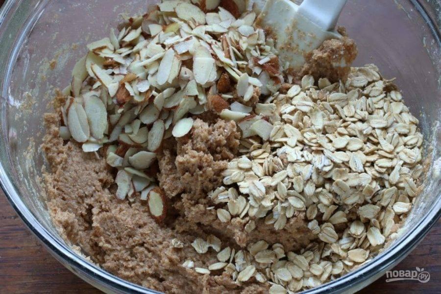 6.Добавьте в тесто овсянку и нарезанный крупно миндаль, перемешайте.