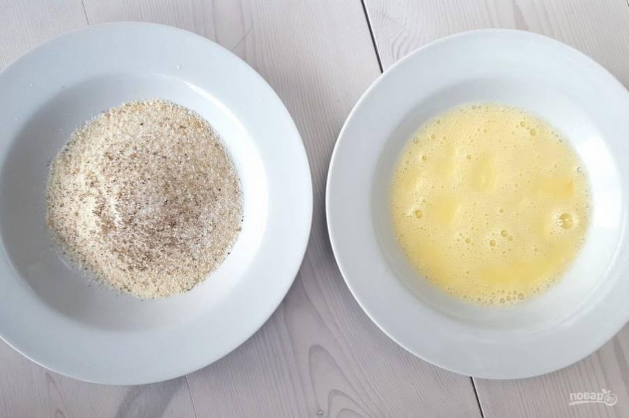 В одну тарелку всыпьте сухари с солью и перцем. Во второй взбейте яйцо.