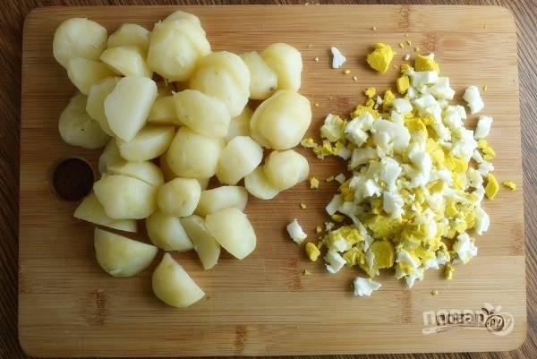 Картофель отварите, очистите, нарежьте на половинки. Яйца отварите, остудите в холодной воде, очистите. Нарежьте мелкими кубиками.