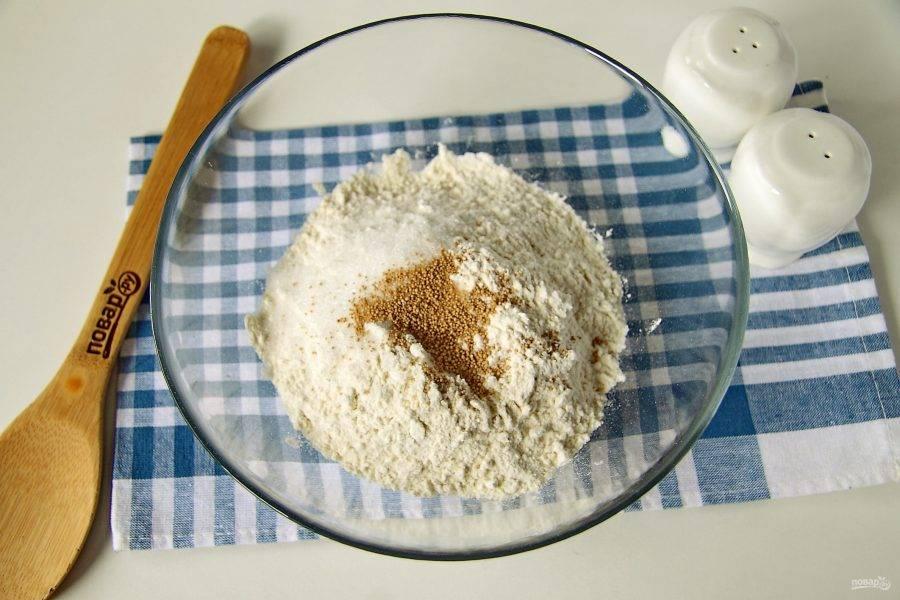 Насыпьте муку в глубокую миску. Добавьте дрожжи и сахар.
