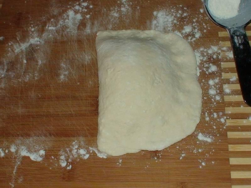 На посыпанную мукой дощечку выкладываем тесто для формирования одного пирожка. Раскатываем из него полукруг. На одну сторону полукруга кладём начинку, другой стороной закрываем.