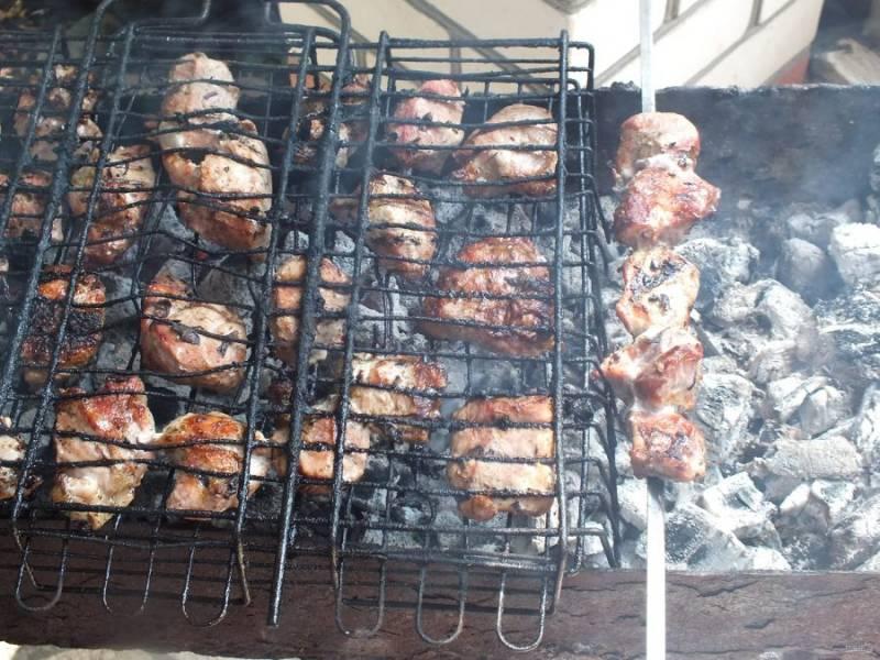 По истечении времени обжарьте мясо на решетке или шампурах на умеренно горячих углях в течение 15-20 минут.