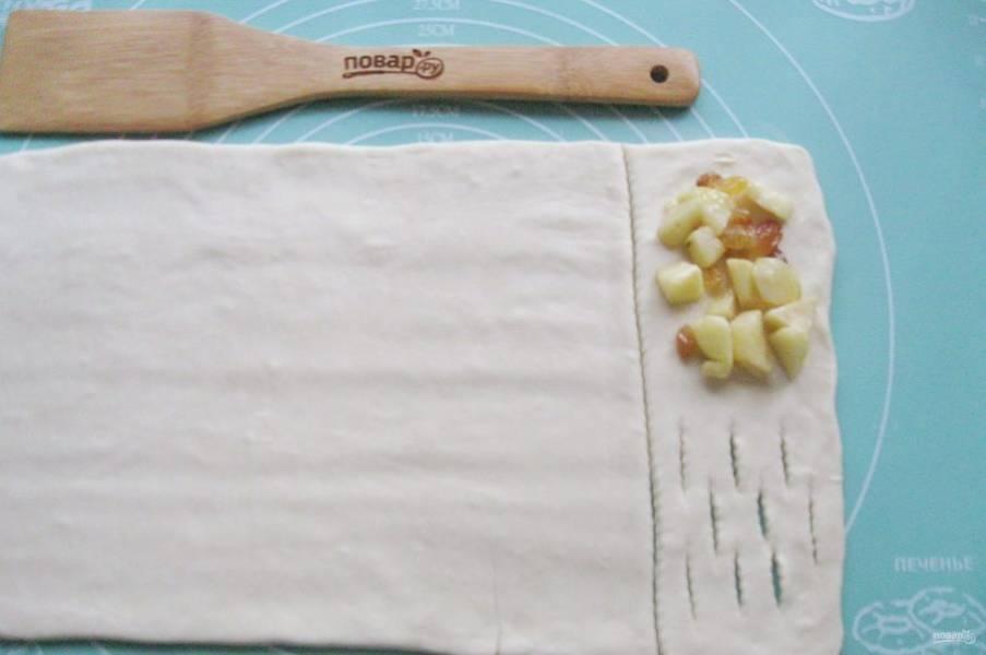 Из теста вырежьте прямоугольник. Визуально разделите на две равные части. Одну часть нарежьте, как показано на фото. На другую часть выложите столовую ложку яблок с изюмом.