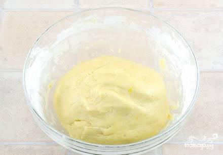 Приступаем к готовке теста. Как всегда начинаем с того, что растираем сливочное масло вместе с сахаром. Затем добавляем взбитый белок (оставшийся от 5-ти яиц), одно яйцо и вторую половину натёртой цедры лимона. Сильно перемешивать не стоит. Добавляем муку и разрыхлитель, на этом этапе следует тщательно замесить тесто ложкой. Скатываем полученное тесто в шарик.
